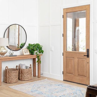 Inspiration for a mid-sized transitional light wood floor and beige floor entryway remodel in Indianapolis with white walls and a light wood front door