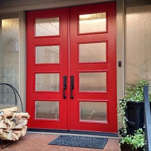 Ejemplo de puerta principal tradicional, grande, con paredes grises, puerta doble y puerta roja