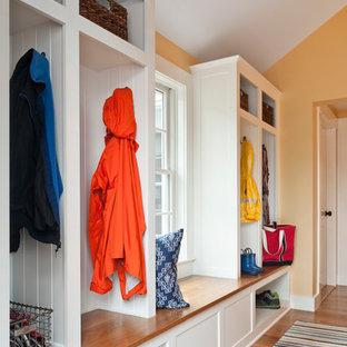 Aménagement d'une entrée contemporaine de taille moyenne avec un mur jaune, un vestiaire et un sol en bois brun.
