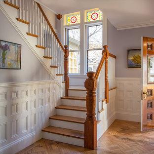 Cette image montre un hall d'entrée victorien avec un mur violet, un sol en bois brun, une porte simple et une porte en bois foncé.