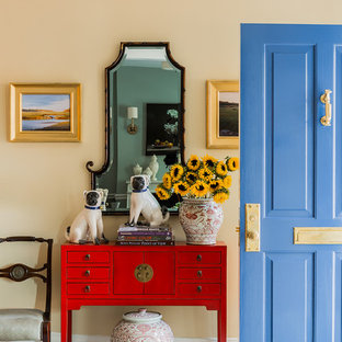 Inspiration for a mid-sized timeless medium tone wood floor and brown floor entryway remodel in Boston with yellow walls and a blue front door