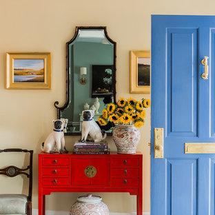 Cette photo montre une porte d'entrée chic de taille moyenne avec un mur jaune, un sol en bois brun, une porte simple, une porte bleue et un sol marron.
