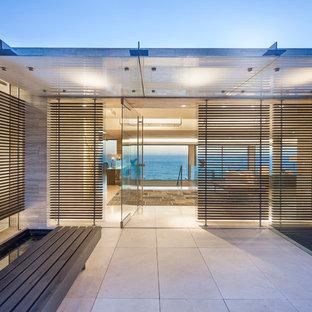 Diseño de puerta principal contemporánea, de tamaño medio, con paredes beige, suelo de piedra caliza, puerta pivotante y puerta de vidrio