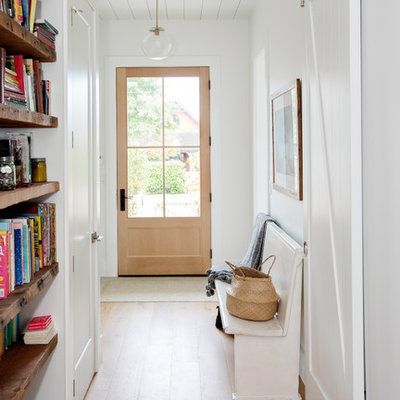 Inspiration for a country medium tone wood floor and brown floor single front door remodel in Vancouver with white walls and a light wood front door