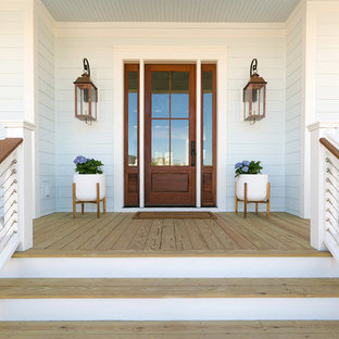 Example of a large cottage light wood floor and beige floor entryway design in Charleston with blue walls and a glass front door