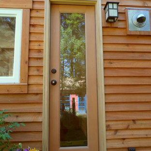 Single front door - small single front door idea in Portland with brown walls and a glass front door