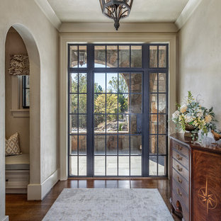 Large tuscan dark wood floor and brown floor entryway photo in Other with a metal front door and beige walls