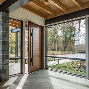 На фото: большое фойе в современном стиле с белыми стенами, полом из известняка, одностворчатой входной дверью, входной дверью из дерева среднего тона, серым полом и деревянными стенами
