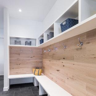 Пример оригинального дизайна: большой тамбур в современном стиле с белыми стенами, полом из сланца, одностворчатой входной дверью и белой входной дверью