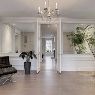 Example of a huge transitional light wood floor double front door design in DC Metro with white walls and a white front door