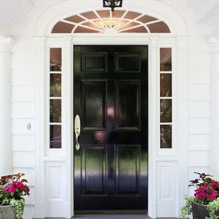 Imagen de puerta principal clásica, grande, con paredes blancas, suelo de pizarra, puerta simple, puerta negra y suelo azul