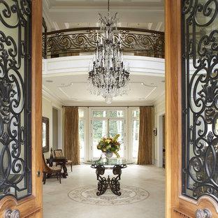 ニューヨークの巨大な両開きドアトラディショナルスタイルのおしゃれな玄関ロビー (ベージュの壁、木目調のドア) の写真