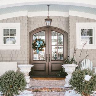 Inredning av en klassisk ingång och ytterdörr, med beige väggar, tegelgolv, en dubbeldörr, en brun dörr och rött golv