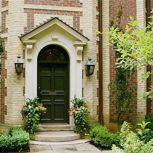 トロントの中くらいの片開きドアトラディショナルスタイルのおしゃれな玄関ドア (黒いドア、赤い壁、コンクリートの床) の写真