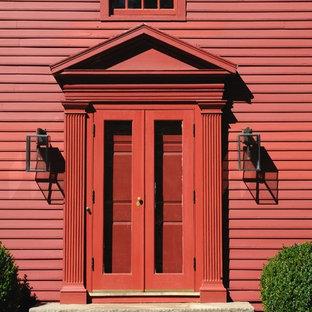 Diseño de puerta principal clásica, de tamaño medio, con paredes rojas, suelo de pizarra, puerta doble y puerta roja