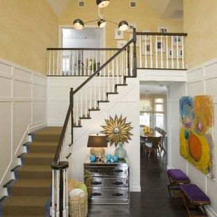 Example of a large classic dark wood floor foyer design in New York with yellow walls