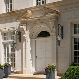 Large elegant limestone floor entryway photo in Atlanta with a white front door and white walls