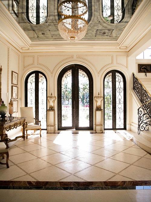 Example Of A Tuscan Travertine Floor Entryway Design In Orlando With A Dark  Wood Front Door