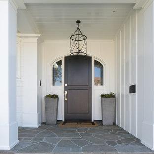 Modelo de puerta principal marinera, de tamaño medio, con paredes blancas, puerta simple y puerta marrón