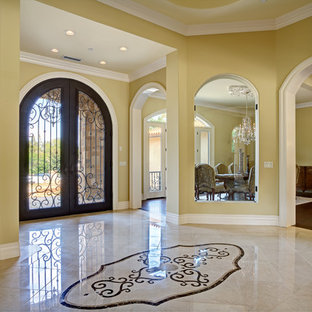 Example of a huge classic marble floor entryway design in San Francisco with yellow walls and a metal front door