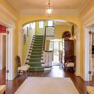 Пример оригинального дизайна: большая прихожая в классическом стиле с желтыми стенами и паркетным полом среднего тона