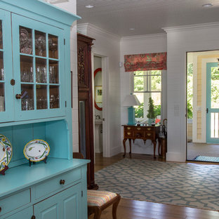 Entryway - mid-sized eclectic medium tone wood floor and brown floor entryway idea in Grand Rapids with white walls and a white front door