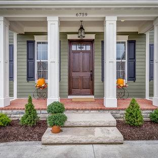 コロンバスの片開きドアトランジショナルスタイルのおしゃれな玄関ドア (緑の壁、濃色木目調のドア) の写真