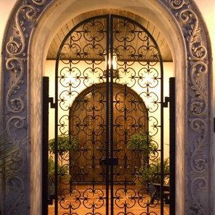 Свежая идея для дизайна: большая прихожая в средиземноморском стиле с бежевыми стенами, полом из терракотовой плитки, двустворчатой входной дверью, входной дверью из темного дерева и коричневым полом - отличное фото интерьера