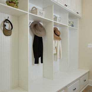 Example of a large classic travertine floor mudroom design in DC Metro with beige walls