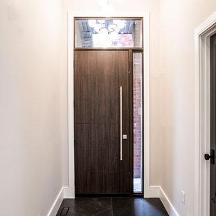 Diseño de distribuidor moderno, de tamaño medio, con paredes grises, suelo de baldosas de porcelana, puerta simple, puerta de madera oscura y suelo negro