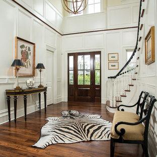 Imagen de distribuidor clásico renovado, grande, con suelo de madera oscura, puerta simple, puerta de madera oscura, paredes amarillas y suelo marrón