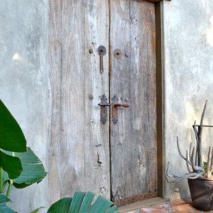 Imagen de puerta principal mediterránea con suelo de baldosas de terracota, puerta doble y puerta de madera en tonos medios