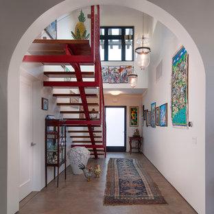 Idéer för mellanstora medelhavsstil hallar, med vita väggar, betonggolv, en enkeldörr och glasdörr