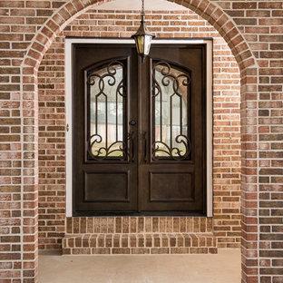 Пример оригинального дизайна: большая входная дверь в стиле современная классика с двустворчатой входной дверью, красными стенами и входной дверью из темного дерева