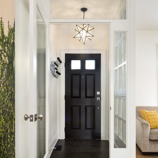 Example of a small transitional granite floor entryway design in Toronto with white walls and a dark wood front door