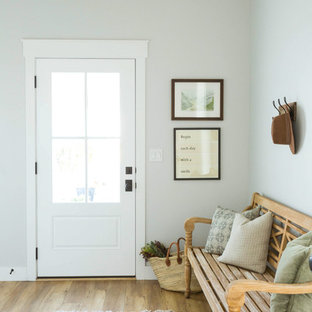 Example of a transitional medium tone wood floor and brown floor entryway design in Salt Lake City with white walls and a white front door