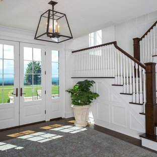Huge transitional dark wood floor and brown floor entryway photo in Other with white walls and a white front door