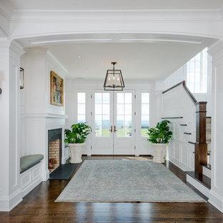 他の地域の巨大な両開きドアトラディショナルスタイルのおしゃれな玄関ロビー (濃色無垢フローリング、白いドア、茶色い床、白い壁) の写真