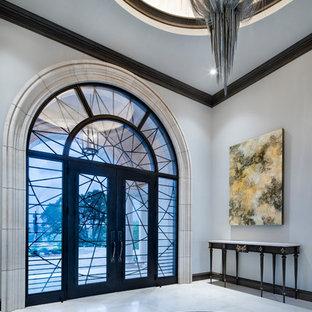Esempio di un grande ingresso mediterraneo con pareti grigie, una porta a due ante, pavimento bianco e una porta in vetro