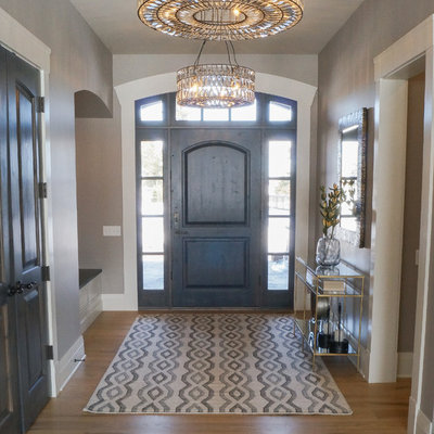 Mid-sized transitional light wood floor and brown floor entryway photo in Other with beige walls and a dark wood front door