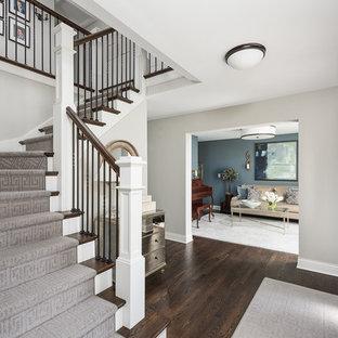 Пример оригинального дизайна: большое фойе в стиле неоклассика (современная классика) с серыми стенами, темным паркетным полом, поворотной входной дверью, входной дверью из темного дерева, коричневым полом и правильным освещением