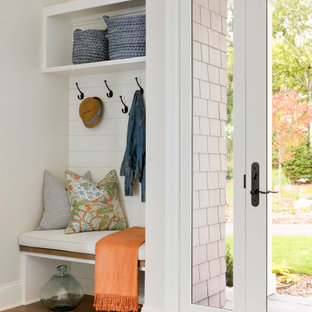 Inspiration for a timeless medium tone wood floor and shiplap wall entryway remodel in Minneapolis with beige walls and a glass front door