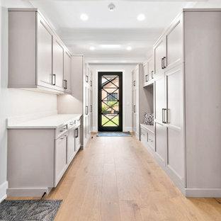 Cette image montre une grand entrée traditionnelle avec un vestiaire, un mur gris, un sol en bois clair, une porte simple, une porte blanche, un sol marron et un plafond à caissons.