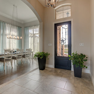 Inspiration for a mid-sized southwestern ceramic floor and brown floor entry hall remodel in Austin with beige walls and a glass front door