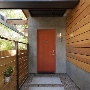Modern inredning av en entré, med en orange dörr