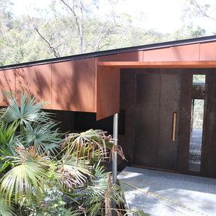 Foto di una porta d'ingresso contemporanea di medie dimensioni con pareti arancioni, una porta a pivot e una porta nera