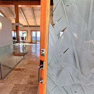 ハワイの大きい片開きドアトロピカルスタイルのおしゃれな玄関ホール (ベージュの壁、セラミックタイルの床、ガラスドア) の写真