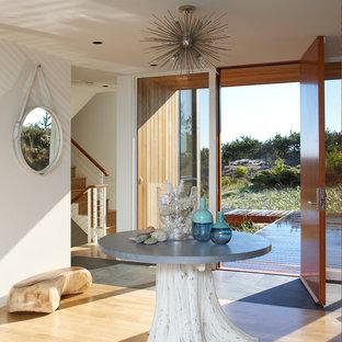 Idée de décoration pour un grand hall d'entrée minimaliste avec un mur blanc, un sol en bois clair, une porte simple, une porte en bois brun et un sol beige.