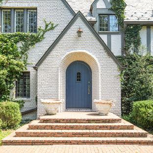 Imagen de puerta principal grande con paredes blancas, puerta simple y puerta azul