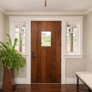 Cette image montre une entrée traditionnelle avec un mur beige, un sol en bambou, une porte simple et une porte en bois brun.